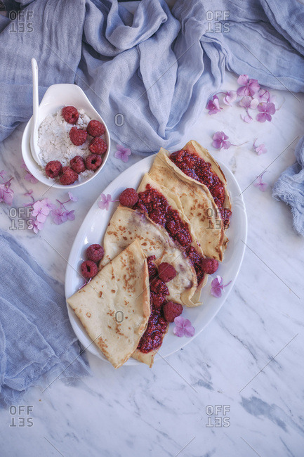 Crepes with raspberry chia jam served on a white plate