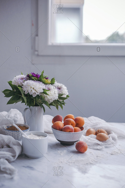 Apricots yogurt cake ingredients on a white marble table