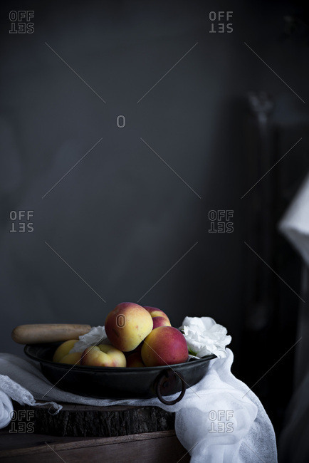 Fresh peaches in a bowl in a rustic kitchen