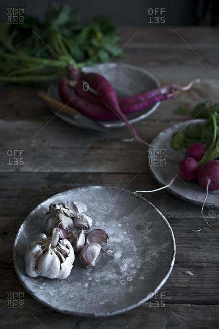 Fresh garlic on a plate in a vintage kitchen