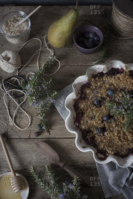 Blueberry, pear and blackberry crumble on a wooden table with ingredients