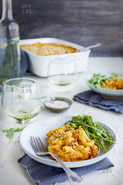 Manchego Piquillo Pepper Mac n Cheese topped with Marcona Almonds. Served with arugula and white wine. Photographed on a white plaster background.