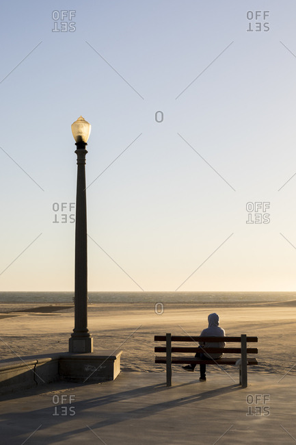 A man sits on a bench by a street lamp on Venice Beach