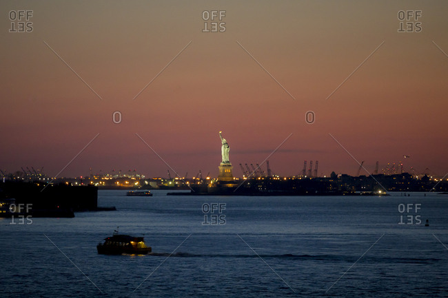 Looking out at the Statue of Liberty at twilight from Brooklyn