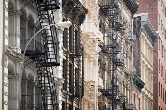 Looking up at fire escapes on buildings of Tribeca in New York City