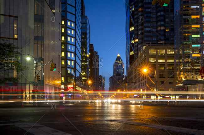 New York City, New York, USA - September 5, 2015: Cars and traffic zoom by on a busy New York City street at night