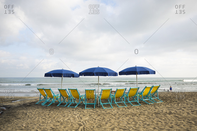 Sayulita, Mexico - April 28, 2016: A cluster of beach chairs and umbrellas on the shore in Sayulita, Mexico