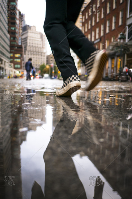 A kid runs through a puddle of water in New York City