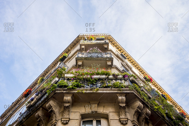 Looking up at corner apartments with balconies filled with flowers in Paris, France