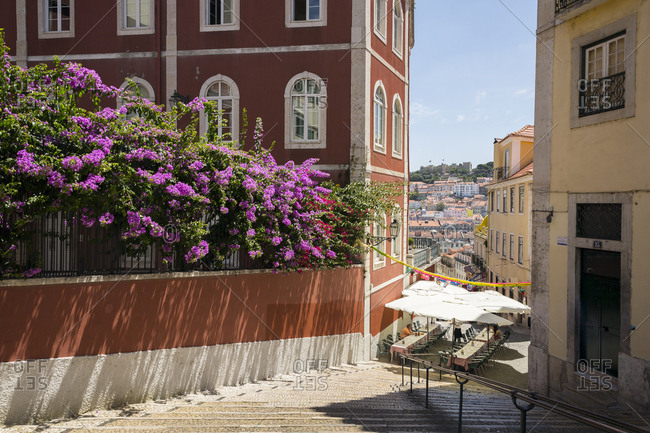 Lisbon, Portugal - June 24, 2015: A sidewalk cafe nestled on a city street with steps and flowers in Lisbon, Portugal