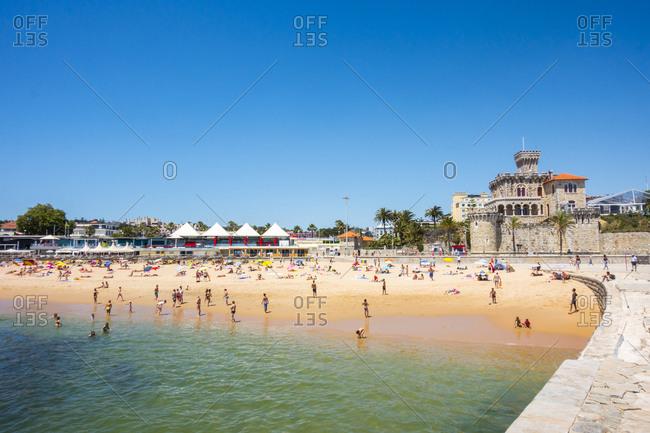 Lisbon, Portugal - June 25, 2015: A summer crowd sun bathes on the beach at Praia do Tamariz a short train ride from Lisbon, Portugal