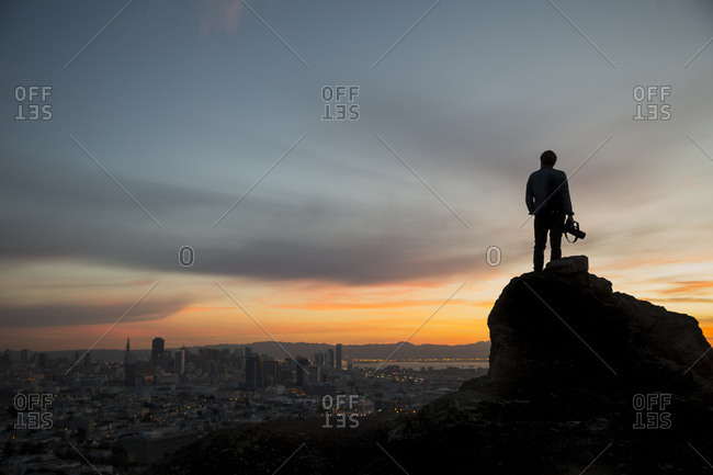 Silhouette of photographer overlooking San Francisco at sunrise from the summit of Buena Vista Park