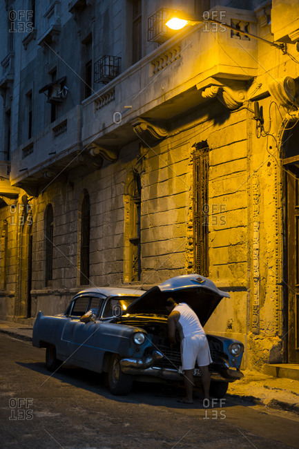 Havana, Cuba - April 30, 2016: Man working on vintage car