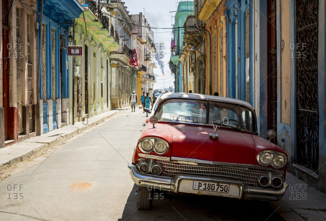 Havana, Cuba - May 1, 2016: Antique car by colorful homes