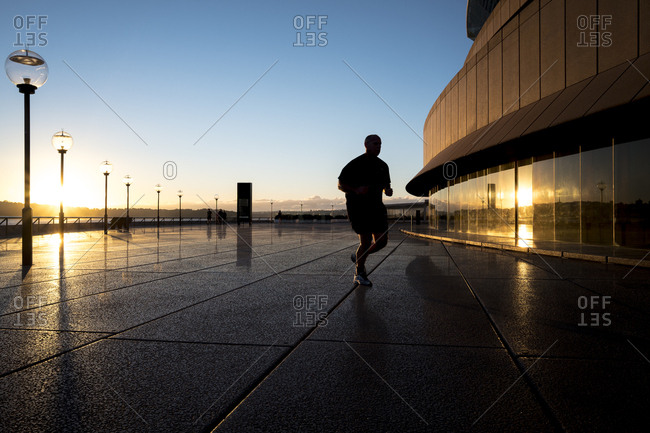 Sydney, Australia - May 15, 2017: Man jogging past Opera House