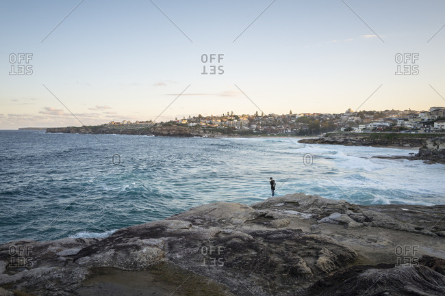 Sydney, Australia - May 21, 2017: A man on rocks at Tamarama Beach