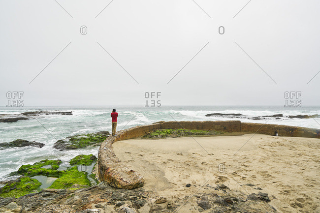 Man standing on the ruins of an oceanfront pool
