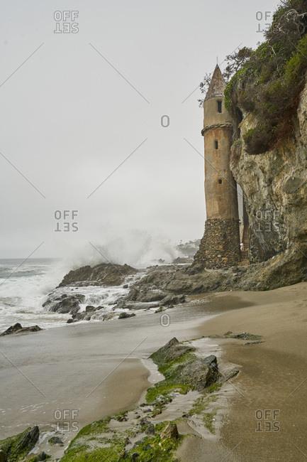 Waves crash on the rocks at the base of Victoria Beach Tower, Laguna Beach, California