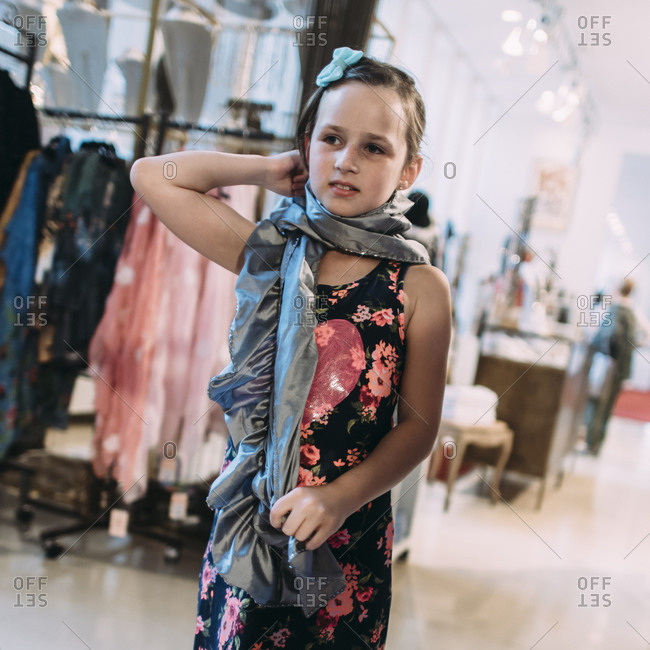 Girl trying on fancy scarf in a store