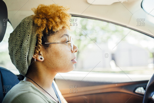 Side view of thoughtful woman sitting in car