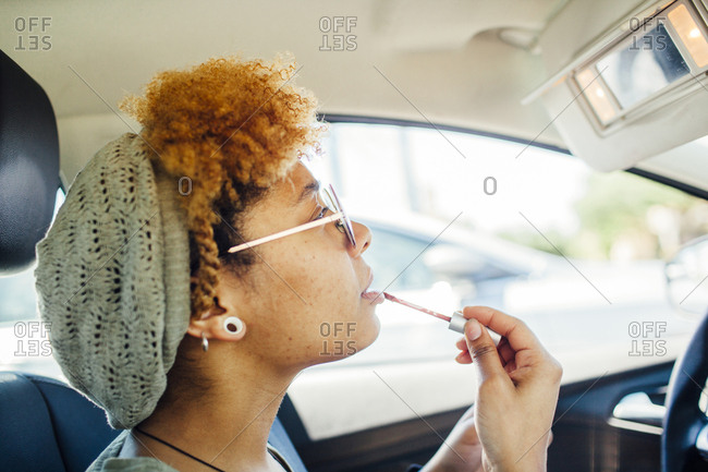 Woman applying lip gloss while sitting in car