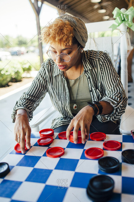 Woman playing checkers while sitting at yard
