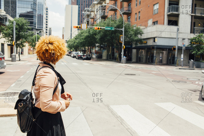 Side view of woman with bag standing on city street during sunny day