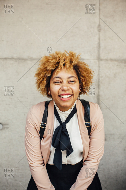 Portrait of happy woman standing against wall
