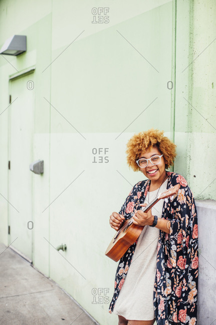 Portrait of happy woman strumming guitar while leaning on wall