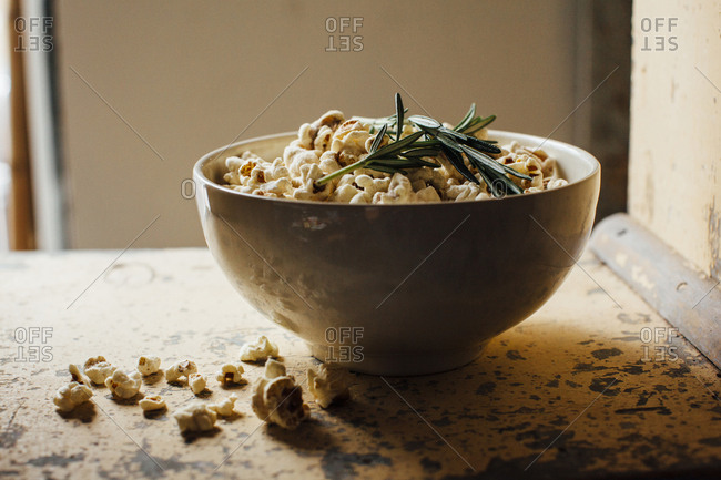 Bowl of popcorn with rosemary on table