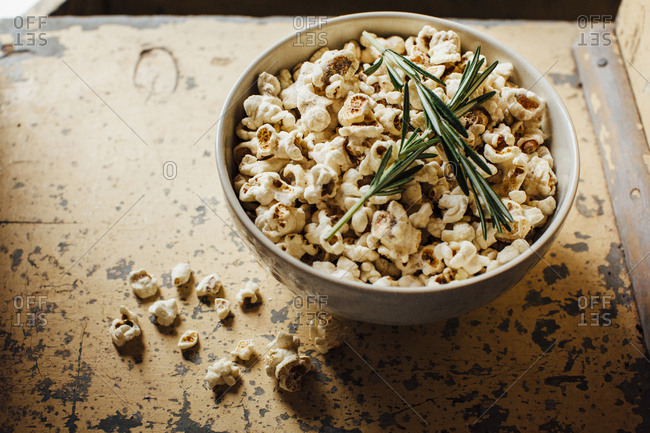 High angle view of popcorn and rosemary in bowl on table