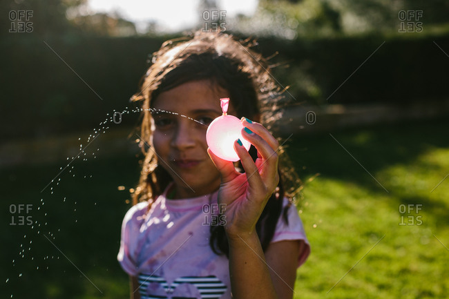 Portrait of girl spraying from water bomb at backyard