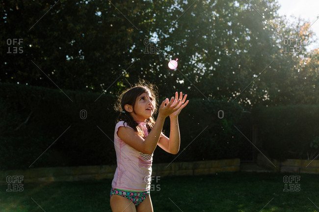 Girl playing with water bomb in backyard
