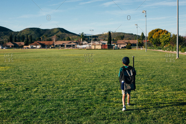 Rear view of boy carrying backpack while walking on grassy field against sky