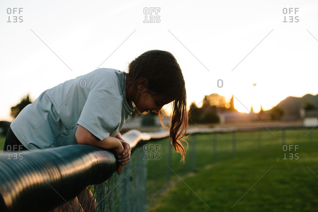 Side view of girl bending over fence at playground during sunset