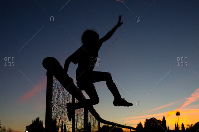Silhouette sporty girl jumping over fence during dusk against sky