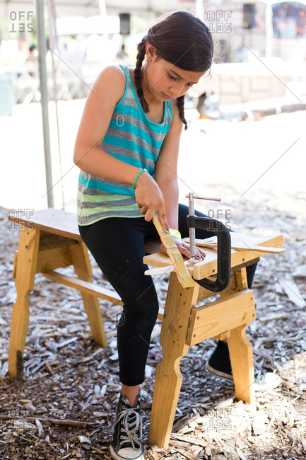 Girl shaping wood while sitting on bench at yard