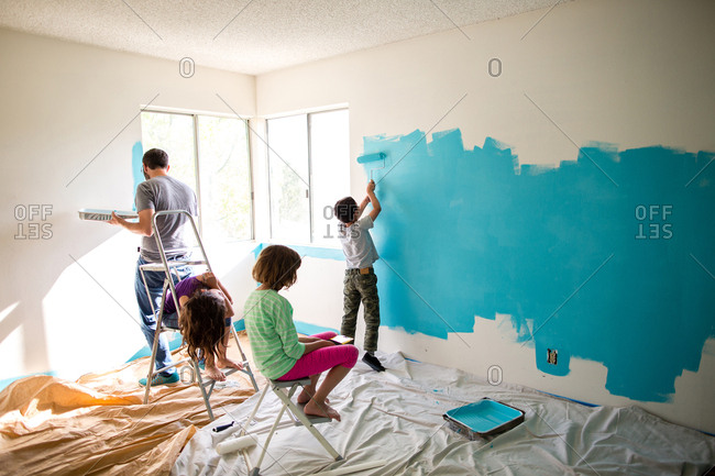 Father and son painting wall while sisters sitting on ladders at home