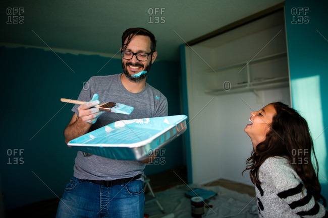 Happy father holding paint tray and brush while daughter laughing at home