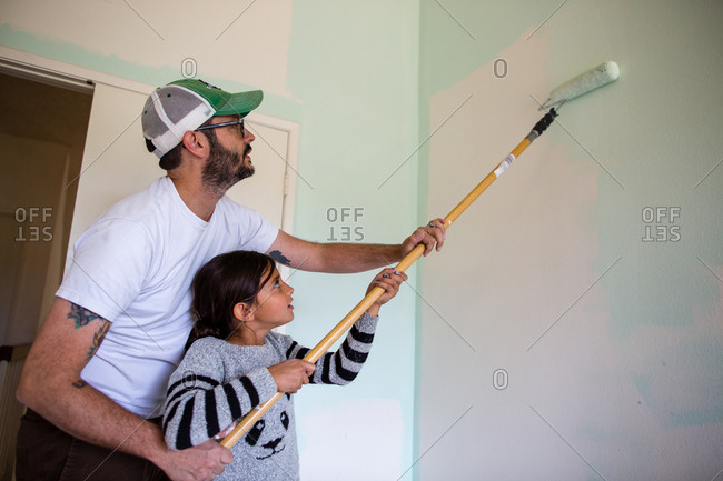 Father helping daughter in painting wall with paint roller at home