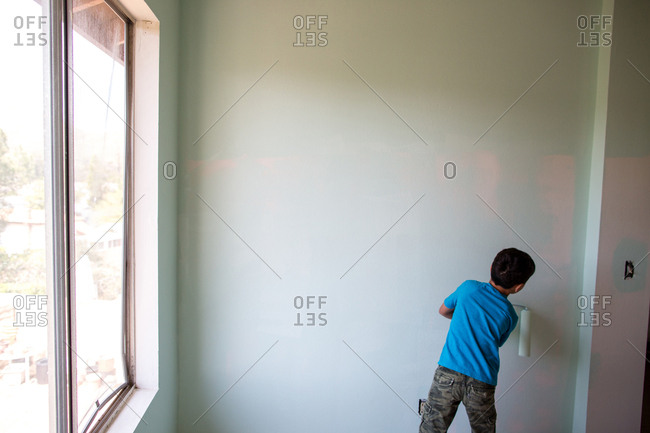 Rear view of boy painting wall with paint roller at home