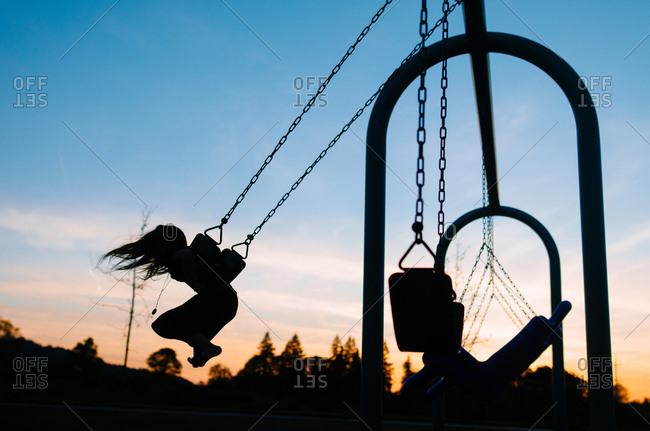 Silhouette girl swinging at playground against sky during dusk