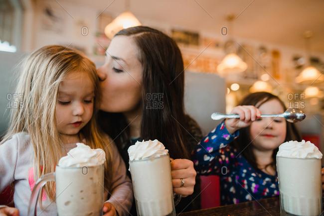 Mother kissing daughter while having milkshake at restaurant table
