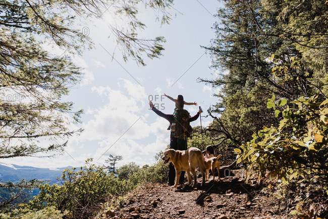 Male hiker carrying daughter while standing by dogs on mountain against sky