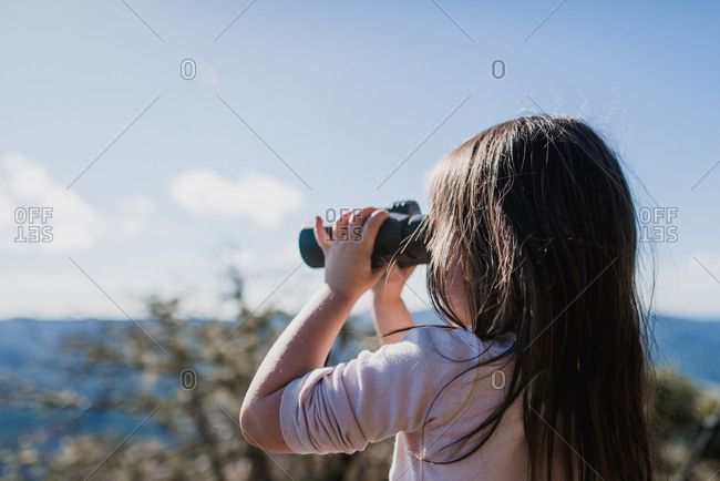 Girl looking through binoculars against sky