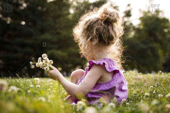 Side view of girl picking flowers while sitting amidst field at park