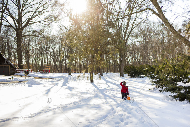 Rear view of boy walking on snow covered field at yard