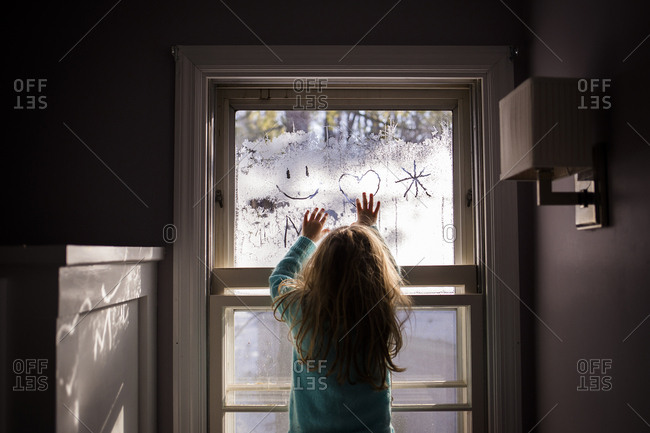 Rear view of girl drawing on condensed window at home