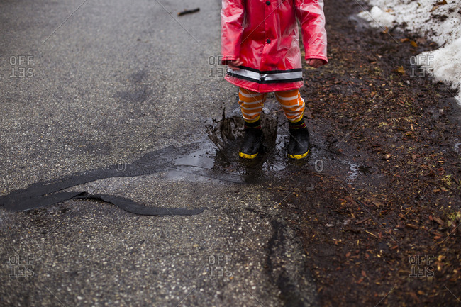 Low section of boy splashing in puddle on street