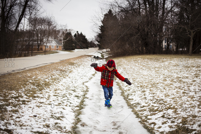 Playful boy walking on snow covered footpath